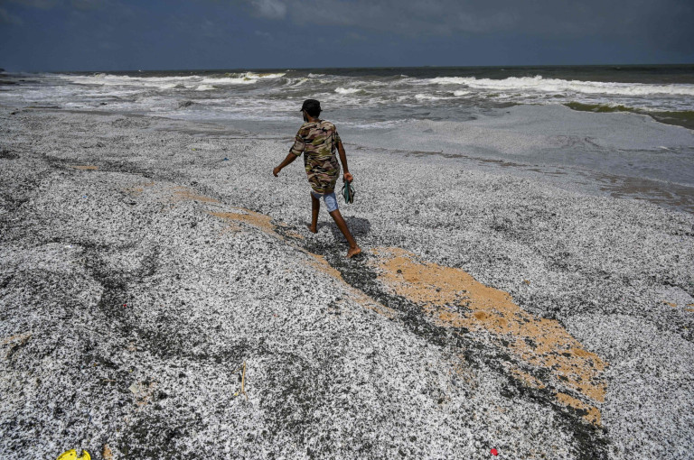 TOPSHOT - A man walks amid debris washed ashore from the Singapore-registered container ship MV X-Press Pearl, which has been burning for the 10th consecutive day in the sea off Sri Lanka's Colombo Harbour, on a beach in Colombo on May 29, 2021. (Photo by ISHARA S. KODIKARA / AFP) (Photo by ISHARA S. KODIKARA/AFP via Getty Images)