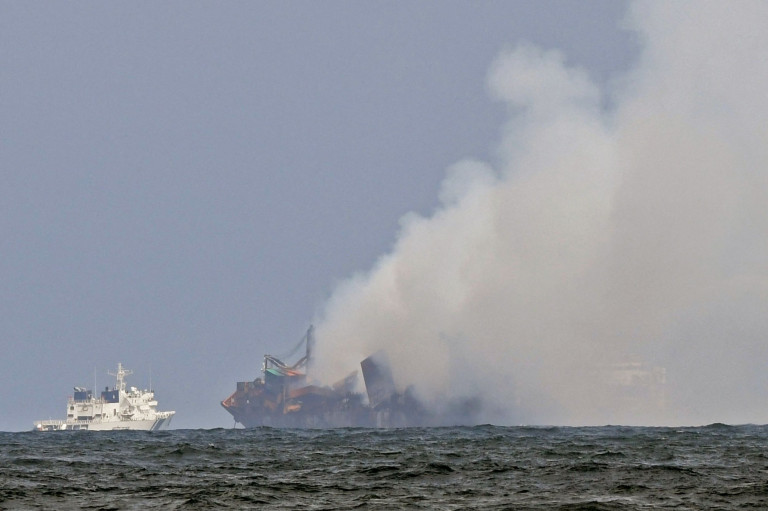 An Indian Coast Guard ship (L) tries to douse off the fire as smoke billows from the Singapore-registered container ship MV X-Press Pearl, which has been burning for the 12th consecutive day in the sea off Sri Lanka's Colombo Harbour, on a beach in Colombo on May 31, 2021. (Photo by Lakruwan WANNIARACHCHI / AFP) (Photo by LAKRUWAN WANNIARACHCHI/AFP via Getty Images)