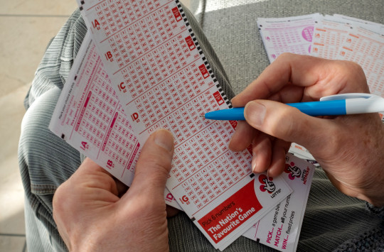 man filling in lotto tickets