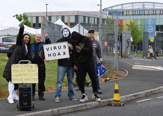 Anti-vaccination protesters stand with placards outside a temporary vaccination centre at the Essa academy in Bolton, northwest England on May 20, 2021. (Photo by Paul ELLIS / AFP) (Photo by PAUL ELLIS/AFP via Getty Images)