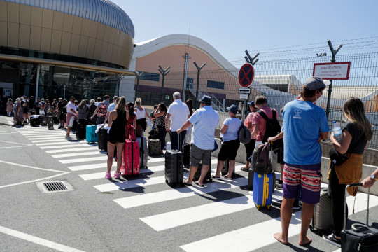 British tourists and residents line up to return to England at Faro airport as Portugal prepares to be added to the amber list on Tuesday
