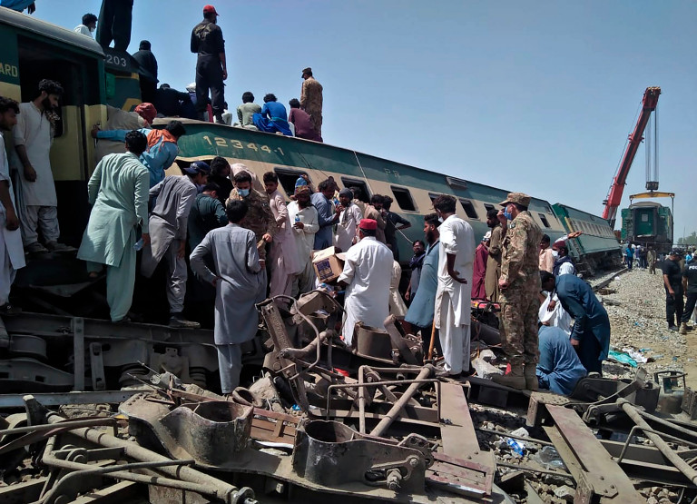 Soldiers and volunteers work at the site of a train collision in Ghotki district in the southern Pakistan, Monday, June 7, 2021. Two express trains collided in southern Pakistan early Monday, killing dozens of passengers, authorities said, as rescuers and villagers worked to pull injured people and more bodies from the wreckage. (AP Photo/Waleed Saddique)