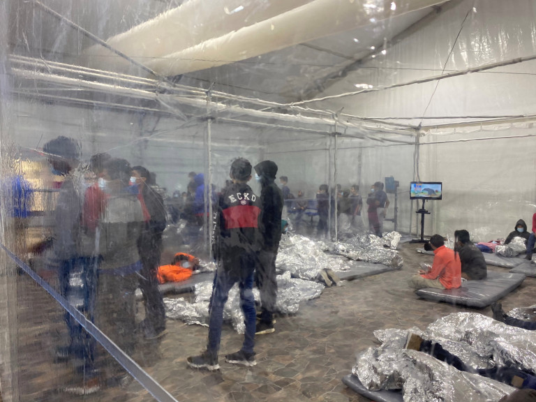 Migrants crowd a room with walls of plastic sheeting at the U.S. Customs and Border Protection temporary processing center in Donna, Texas, U.S. in a recent photograph released March 22, 2021. Office of Congressman Henry Cuellar (TX-28)/Handout via REUTERS THIS IMAGE HAS BEEN SUPPLIED BY A THIRD PARTY.
