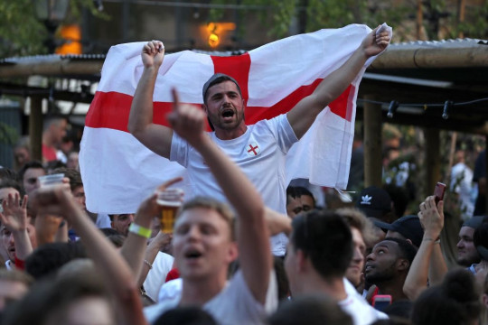 An England supporter holds up a St George's cross flag as the atmosphere builds in the Flat Iron Square pub in London ahead of the match in Kaliningrad, where England and Belgium play to decide the winner of Group G in the Russia 2018 World Cup on June 28, 2018. (Photo by Daniel LEAL-OLIVAS / AFP) (Photo credit should read DANIEL LEAL-OLIVAS/AFP via Getty Images)