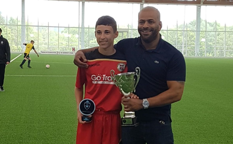 Richard Laleye with his son Nathan, who is wearing a football kit. They are at an indoor football event and both holding trophies
