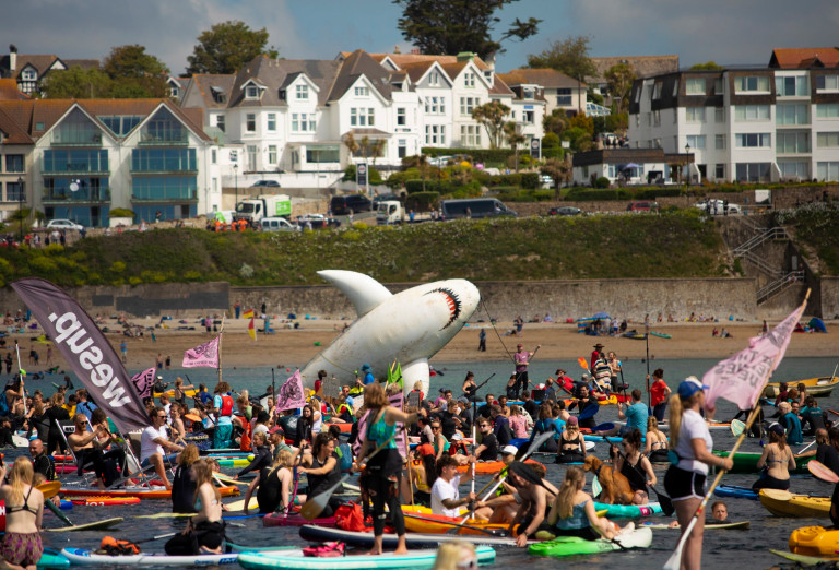 epa09264655 Paddleboarders and surfers take part in a paddle out to raise awareness for climate action in the sea at Gyllyngvase beach, in Falmouth, Cornwall, Britain 12 June 2021. Britain is hosting the G7 summit in Cornwall in from 11 to 13 June 2021. EPA/JON ROWLEY