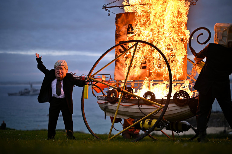 ST IVES, UNITED KINGDOM ??? JUNE 11: An Ocean Rebellion activist dressed as British Prime Minister Boris Johnson sets fire to a boat during the G7 summit in Cornwall on June 11, 2021 in St Ives, Cornwall, England. Environmental Protest Groups gather in Cornwall as the UK Prime Minister, Boris Johnson, hosts leaders from the USA, Japan, Germany, France, Italy and Canada at the G7 Summit in Carbis Bay. This year the UK has invited Australia, India, South Africa and South Korea to attend the Leaders' Summit as guest countries as well as the EU. Protest groups hope to highlight their various causes to the G7 leaders and a global audience as the eyes of the world focus on Cornwall during the summit. (Photo by Jeff J Mitchell/Getty Images)