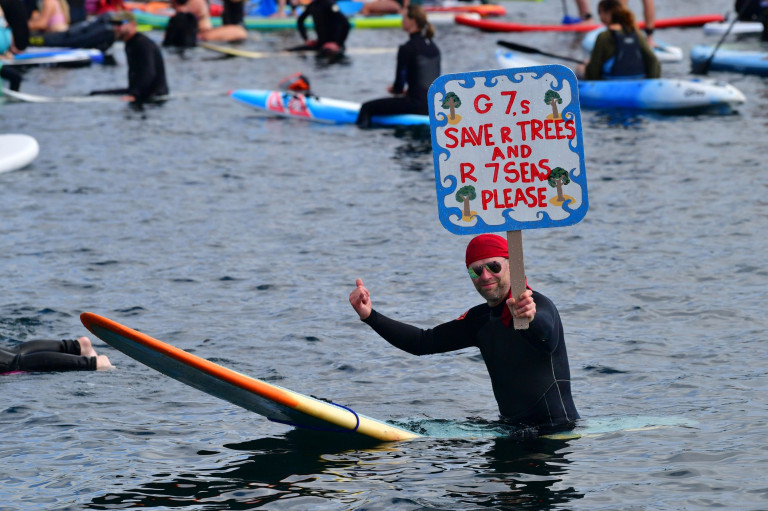 Protesters take part in a paddle out, organised by Surfers Against Sewage, on Gyllyngvase Beach near Falmouth, during the G7 summit in Cornwall. Picture date: Saturday June 12, 2021. PA Photo. See PA story POLITICS G7. Photo credit should read: Ben Birchall/PA Wire