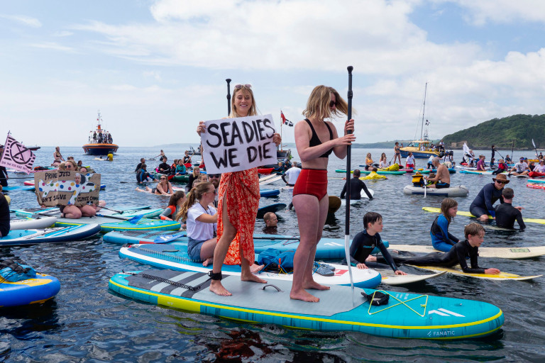 FALMOUTH, ENGLAND - JUNE 12 : A mass gathering of G7 paddle-out protesters organised by the environmental charity Surfers Against Sewage, at Gyllyngvase Beach on June 12, 2021 in Falmouth, England. Environmental Protest Groups gather in Cornwall as the UK Prime Minister, Boris Johnson, hosts leaders from the USA, Japan, Germany, France, Italy and Canada at the G7 Summit in Carbis Bay. This year the UK has invited Australia, India, South Africa and South Korea to attend the Leaders' Summit as guest countries as well as the EU. Protest groups hope to highlight their various causes to the G7 leaders and a global audience as the eyes of the world focus on Cornwall during the summit. (Photo by Hugh Hastings/Getty Images)