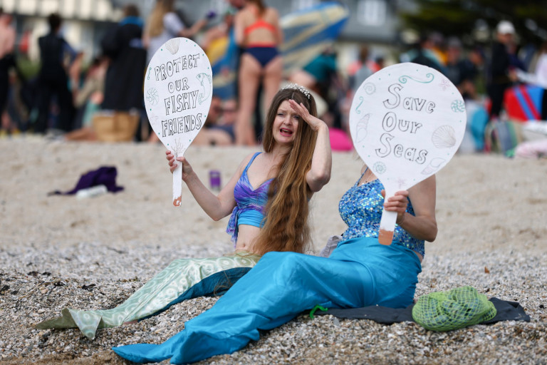 Demonstrators hold signs in a protest in Gyllyngvase beach, Falmouth, during the G7 summit in Cornwall, Britain, June 12, 2021. REUTERS/Tom Nicholson