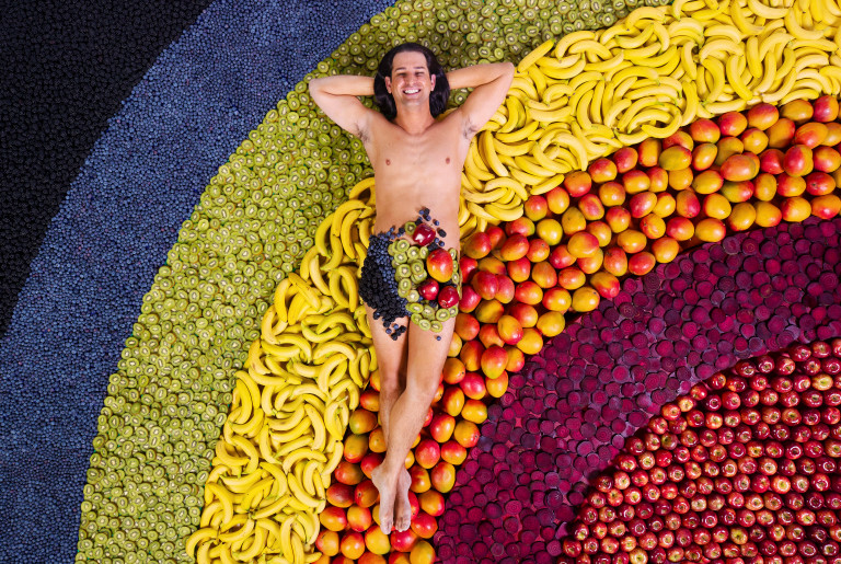 Ollie naked on a pile of fruit