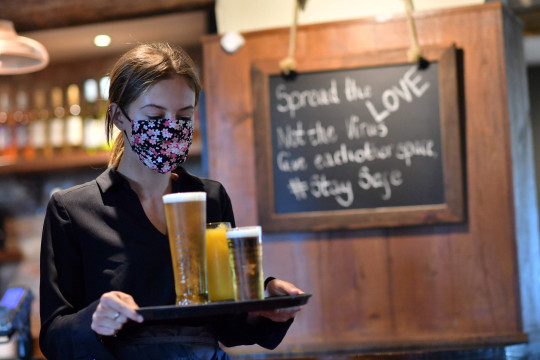 A staff member wears a face mask as she serves customers at the The Shy Horse pub