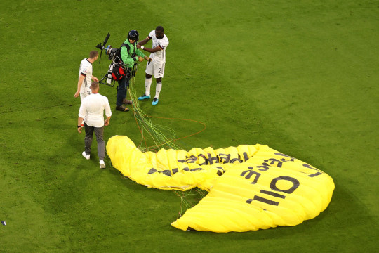 MUNICH, GERMANY - JUNE 15: A greenpeace protester and pitch invader is helped up by Antonio Ruediger of Germany on the pitch prior to the UEFA Euro 2020 Championship Group F match between France and Germany at Football Arena Munich on June 15, 2021 in Munich, Germany. (Photo by Alexander Hassenstein/Getty Images)