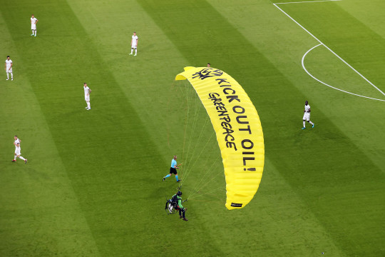 epa09274405 A Greenpeace activist lands with a parachute on the pitch prior to the UEFA EURO 2020 group F preliminary round soccer match between France and Germany in Munich, Germany, 15 June 2021. EPA/Alexander Hassenstein / POOL (RESTRICTIONS: For editorial news reporting purposes only. Images must appear as still images and must not emulate match action video footage. Photographs published in online publications shall have an interval of at least 20 seconds between the posting.)