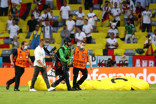 MUNICH, GERMANY - JUNE 15: A greenpeace protester and pitch invader is removed from the pitch by stewards after flying in to the stadium prior to the UEFA Euro 2020 Championship Group F match between France and Germany at Football Arena Munich on June 15, 2021 in Munich, Germany. (Photo by Kai Pfaffenbach - Pool/Getty Images)