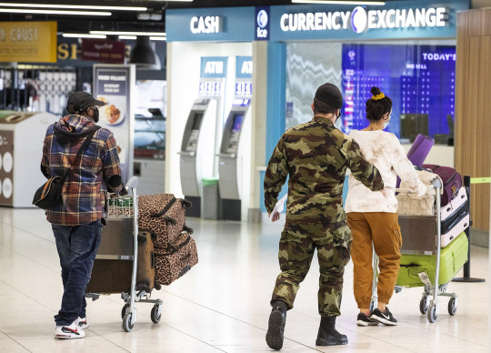 A member of the defence forces escorts passengers from Terminal 1 arrivals hall at Dublin Airport as the State??s mandatory quarantine system was extended on Thursday to include the US, Belgium, France and Italy. Picture date: Thursday April 15, 2021. See PA story IRISH Coronavirus.