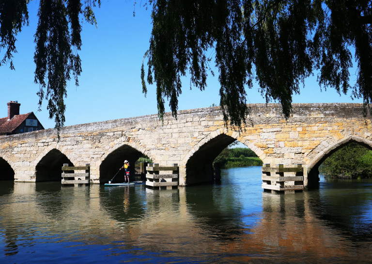 A stand up paddleboarder travels under Tayntons stone bridge on the River Thames at Newbridge, Oxfordshire today