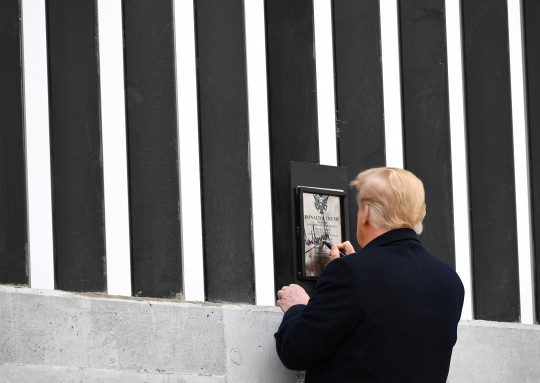 US President Donald Trump signs a plaque as he tours a section of the border wall in Alamo, Texas, on January 12, 2021. (Photo by MANDEL NGAN / AFP) (Photo by MANDEL NGAN/AFP via Getty Images)