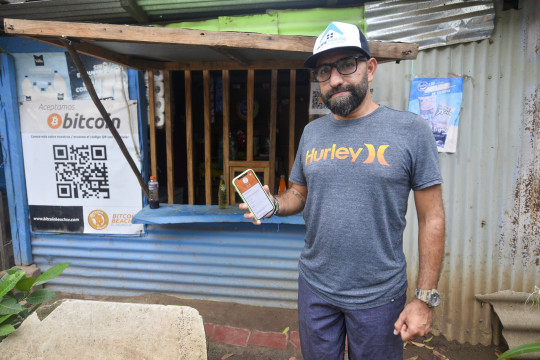 A man holds up a phone displaying a bitcoin wallet app in Chiltuipan, El Salvador. (Getty)
