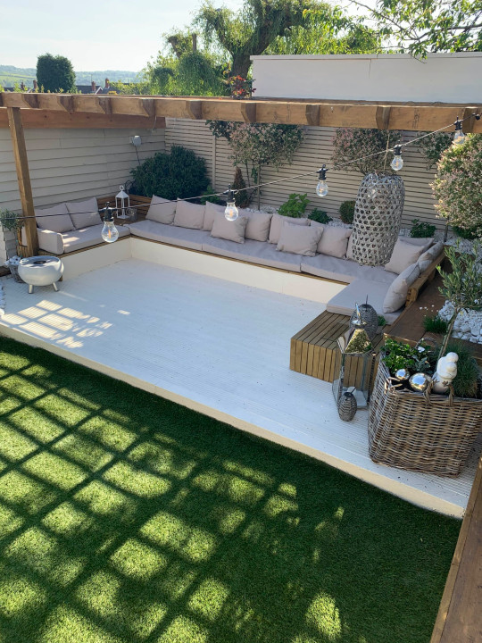@home_joyr / CATERS NEWS - (PICTURED The seating area) A DIY savvy mum has saved over ??25,000 by renovating her garden by herself. Mum-of-two Joy Rodriguez-Adams, 42, from Stoke, Staffordshire, first moved into the detached property more than a decade a go. Joy decided to completely transform the outdated, dull garden into a stunning outdoor paradise and set to work in the first lockdown - adding a large seating area, extending the decking and building their very own outdoor bar called The Tipsy Cow. And the family have just completed the impressive outdoor space, adding their very own built in BBQ and artificial grass to complete the modern look. SEE CATERS COPY