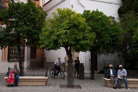 People wearing face masks to help curb the spread of the coronavirus, sit on benches in Seville, Spain, Thursday, June 17, 2021. The city is hosting the games of Group E as well one of the round of 16 for the Euro 2020 soccer championship. (AP Photo/Thanassis Stavrakis)