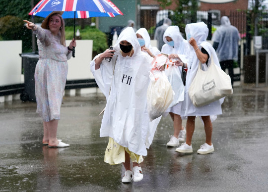 Racegoers wear ponchos to shield themselves from the rain as they arrive on day four of Royal Ascot