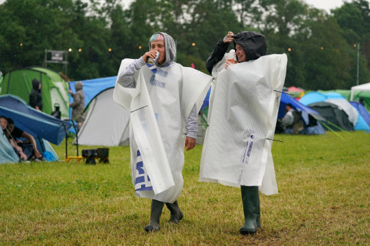 People cover up from the rain on the first day of Download Festival