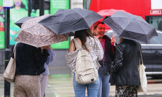 A group of friends shelter under umbrellas as they walk through Piccadilly, London. Picture date: Friday June 18, 2021. PA Photo. See PA story WEATHER Summer. Photo credit should read: Jonathan Brady/PA Wire