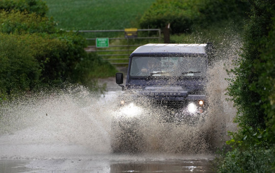 A car drives through a flooded road near Chesham, Buckinghamshire as rain and thunderstorms are set to sweep the South East in the coming days. Picture date: Friday June 18, 2021. PA Photo. The Environment Agency has issued 17 flood alerts, where flooding is possible in London and surrounding areas, and Kent. See PA story WEATHER Wet. Photo credit should read: Steve Parsons/PA Wire