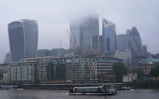 A Thames City Cruises vessel passes by a mist enshrouded City of London. Picture date: Friday June 18, 2021. PA Photo. See PA story WEATHER Summer. Photo credit should read: Jonathan Brady/PA Wire