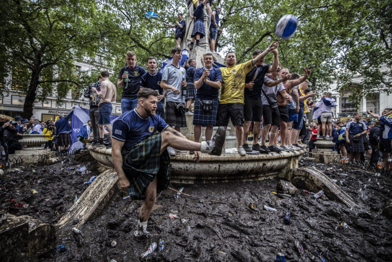 Scottish fans in kilts kicking a ball in the fountain at Leicester Square.  London's cleaners will spend today cleaning Leicester Square after Scottish football fans took over the West End before and after the Euro 2020 game.