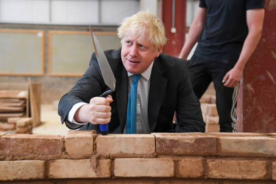Britain's Prime Minister Boris Johnson reacts as lays bricks whilst talking with students during his visit to Exeter College in Exeter, southwest England on September 29, 2020. (Photo by Finnbarr Webster / POOL / AFP) (Photo by FINNBARR WEBSTER/POOL/AFP via Getty Images)