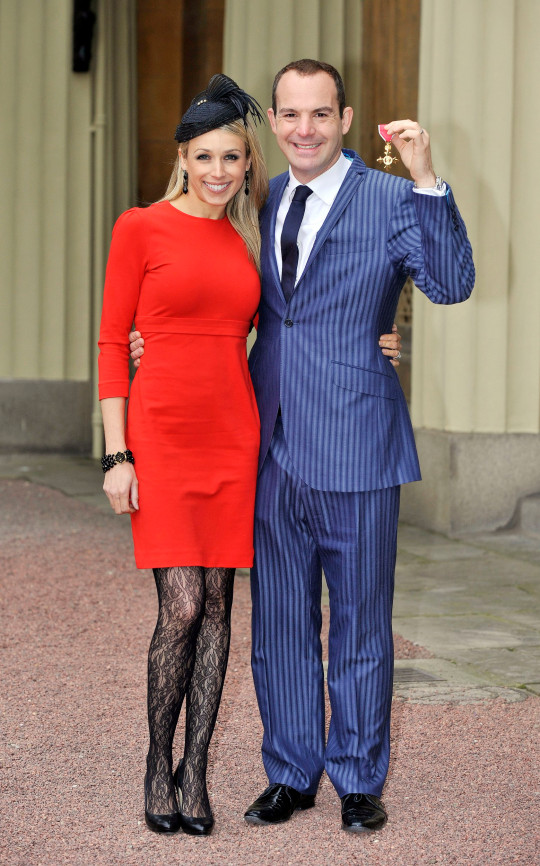 Money Saving Expert Martin Lewis with his Order of the British Empire (OBE) medal presented to him by the Princess Royal alongside his partner Lara Lewington