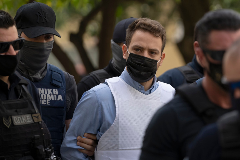 Helicopter pilot Babis Anagnostopoulos, center, escorted by police officers arrives to the prosecutor's office at a court to give evidence, in Athens, Tuesday, June 22, 2021.