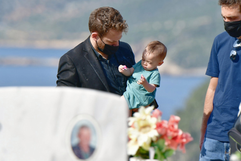 Charalambos (Babis) Anagnostopoulos with his 11 month old daughter at the burial of Caroline Crouch on the island of Alonissos in Greece.