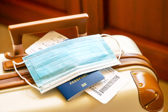 Travel suitcase, passport, air ticket and facial mask