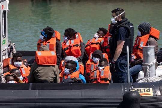 Border Force officials guide newly arrived migrants to a holding facility after being picked up in a dinghy in the English Channel on June 24, 2021 in Dover, England.