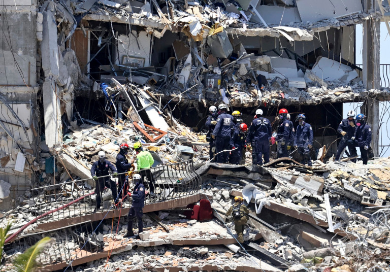 Search and rescue personnel search for survivors through the rubble at the Champlain Towers South in Surfside, Fla., Sunday, June 27, 2021. The apartment building partially collapsed on Thursday, June 24. (David Santiago/Miami Herald via AP)