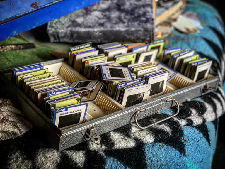 DEVON, UK: Film slides of pictures that were taken by the former owner of the property. THE MOMENT an urban explorer comes across an abandoned cottage full of photo slides of tribal communities taken from around the world and dusty old books has been captured on camera. One photo from the exploration showed the living room of the house, crammed full of wooden stalls, a television from the 1990s and a cast-iron log burner. In a second picture a fascinating set of photo slides from the former owner?s travels to the far east could be seen. In another, photos of what appeared to be the occupant?s grandchildren and pets could be seen on the mantelpiece of the property. The Devon-based abandoned cottage was visited by former plumber turned full time urban explorer Colin Smith (36) from Hampshire, UK who goes by the name The Urban Explorer on YouTube. From the labels on old food, Colin estimated that the property has been left abandoned for at least 20 years. Mediadrumworld.com/Colin Smith