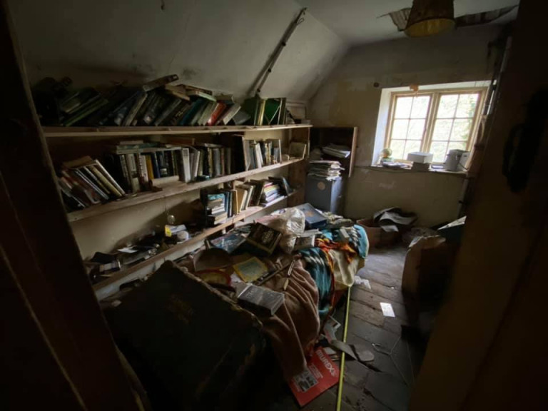 DEVON, UK: Books line the shelves of the property. THE MOMENT an urban explorer comes across an abandoned cottage full of photo slides of tribal communities taken from around the world and dusty old books has been captured on camera. One photo from the exploration showed the living room of the house, crammed full of wooden stalls, a television from the 1990s and a cast-iron log burner. In a second picture a fascinating set of photo slides from the former owner?s travels to the far east could be seen. In another, photos of what appeared to be the occupant?s grandchildren and pets could be seen on the mantelpiece of the property. The Devon-based abandoned cottage was visited by former plumber turned full time urban explorer Colin Smith (36) from Hampshire, UK who goes by the name The Urban Explorer on YouTube. From the labels on old food, Colin estimated that the property has been left abandoned for at least 20 years. Mediadrumworld.com/Colin Smith