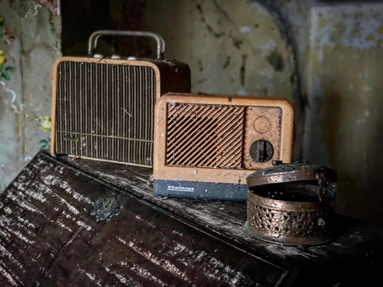 DEVON, UK: An old-style radio sits on the sideboard. THE MOMENT an urban explorer comes across an abandoned cottage full of photo slides of tribal communities taken from around the world and dusty old books has been captured on camera. One photo from the exploration showed the living room of the house, crammed full of wooden stalls, a television from the 1990s and a cast-iron log burner. In a second picture a fascinating set of photo slides from the former owner?s travels to the far east could be seen. In another, photos of what appeared to be the occupant?s grandchildren and pets could be seen on the mantelpiece of the property. The Devon-based abandoned cottage was visited by former plumber turned full time urban explorer Colin Smith (36) from Hampshire, UK who goes by the name The Urban Explorer on YouTube. From the labels on old food, Colin estimated that the property has been left abandoned for at least 20 years. Mediadrumworld.com/Colin Smith