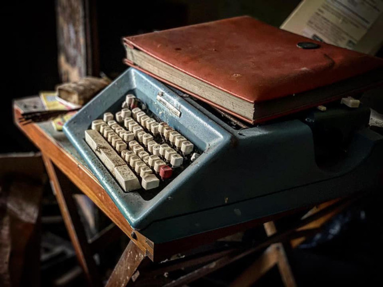 DEVON, UK: A typewriter that has been left behind in the property. THE MOMENT an urban explorer comes across an abandoned cottage full of photo slides of tribal communities taken from around the world and dusty old books has been captured on camera. One photo from the exploration showed the living room of the house, crammed full of wooden stalls, a television from the 1990s and a cast-iron log burner. In a second picture a fascinating set of photo slides from the former owner?s travels to the far east could be seen. In another, photos of what appeared to be the occupant?s grandchildren and pets could be seen on the mantelpiece of the property. The Devon-based abandoned cottage was visited by former plumber turned full time urban explorer Colin Smith (36) from Hampshire, UK who goes by the name The Urban Explorer on YouTube. From the labels on old food, Colin estimated that the property has been left abandoned for at least 20 years. Mediadrumworld.com/Colin Smith