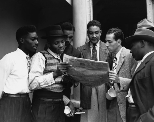 Some of the 482 Jamaicans emigrating to the UK read a newspaper on board the ex-troopship Empire Windrush which arrived at Tilbury. UK. (Photo by ?? Hulton-Deutsch Collection/CORBIS/Corbis via Getty Images)