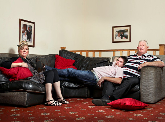George Gilbey, centre, with his mother Linda and stepfather Pete McGarry, who are among the fans favourites on cult Channel 4 series Gogglebox. Lying on the sofa, giving his take on the day?s TV in the voice that has seen him dubbed ?Squeaky?, George Gilbey is a favourite with Gogglebox fans.