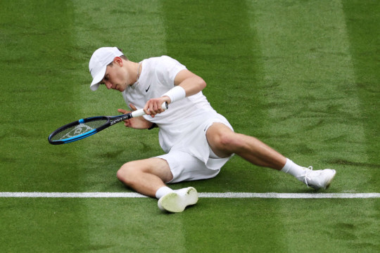 Jack Draper of Great Britain falls in his Men's Singles First Round match against Novak Djokovic of Serbia during Day One of The Championships - Wimbledon 2021 at All England Lawn Tennis and Croquet Club on June 28, 2021 in London, England.