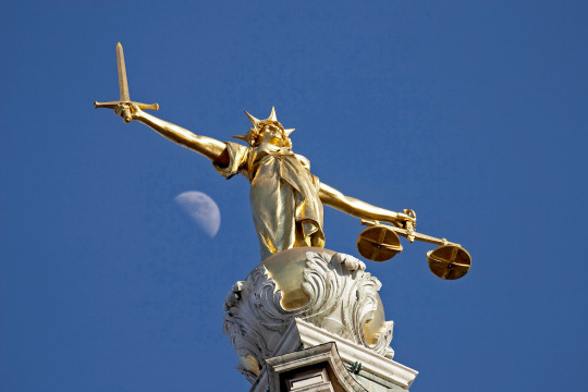 The statue of Justice at The Old Bailey, London. With a sword in one hand and scales in the other this statue of justice on top of the Old Bailey has one difference to many other similar pieces - in this case Justice herself has no blindfold. The sword stands for the power to punish, and the balance standing for equity.