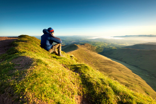Hiker looking over the Brecon Beacons from Pen y Fan