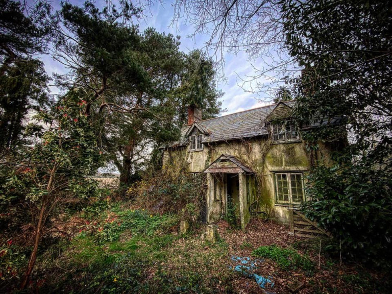 DEVON, UK: An exterior view of the property. THE MOMENT an urban explorer comes across an abandoned cottage full of photo slides of tribal communities taken from around the world and dusty old books has been captured on camera. One photo from the exploration showed the living room of the house, crammed full of wooden stalls, a television from the 1990s and a cast-iron log burner. In a second picture a fascinating set of photo slides from the former owner?s travels to the far east could be seen. In another, photos of what appeared to be the occupant?s grandchildren and pets could be seen on the mantelpiece of the property. The Devon-based abandoned cottage was visited by former plumber turned full time urban explorer Colin Smith (36) from Hampshire, UK who goes by the name The Urban Explorer on YouTube. From the labels on old food, Colin estimated that the property has been left abandoned for at least 20 years. Mediadrumworld.com/Colin Smith