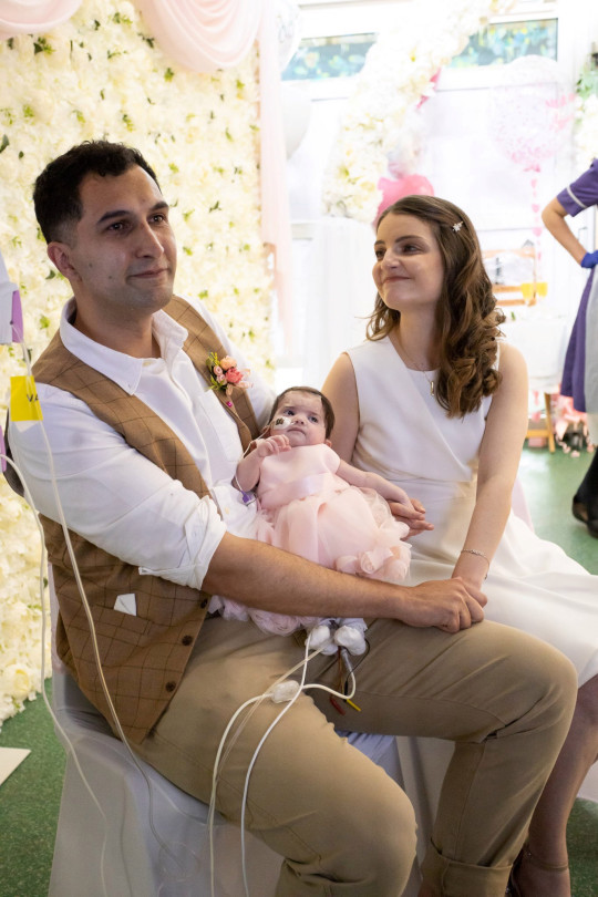Karim Rezaie, 38, psychological therapist and Louise Rezaie, 30, psychological well-being practitioner - on their wedding day with their baby daughter Layla as the bridesmaid