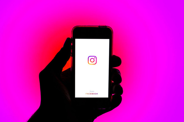 In this photo illustration, the Instagram app is seen displayed in front of a glowing pink background